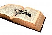 stock photo of hematite  - The old book with a beaded ornament on a turn of pages - JPG