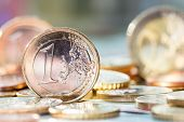 picture of coins  - One euro coin on pile of euro coins in background - JPG