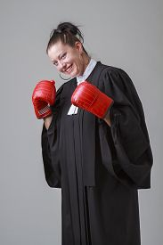 stock photo of toga  - Woman in her thirties wearing a canadian lawyer toga knocking back her fist to punch - JPG