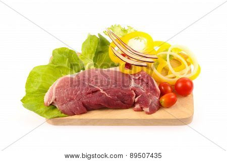 Raw Pork Meat  With Vegetable On Chopping Block
