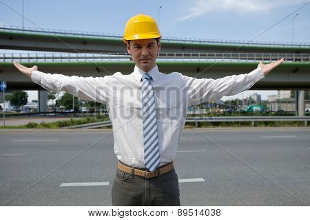 Portrait of architect in hardhat with arm raised at construction site