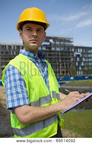 Architect using clipboard at construction site