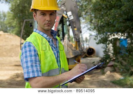 Portrait of architect using clipboard at construction site