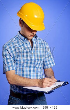 Architect in yellow hardhat writing on clipboard