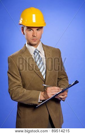 Portrait of businessman in yellow hardhat writing on clipboard