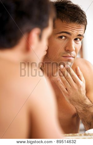 Reflection of young man in mirror with hand on chin