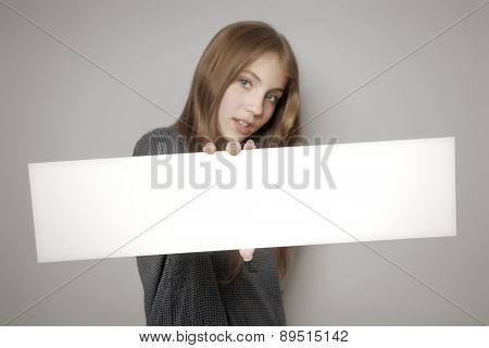 An image of a beautiful teenage girl holding a white board