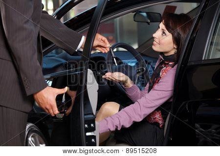 Car salesman giving the car keys to a young woman