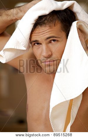 Portrait of young man drying hair with towel
