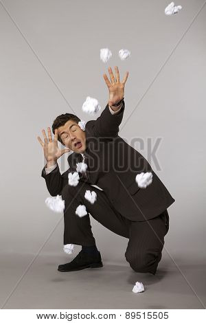 Young caucasian businessman under paper ball attack