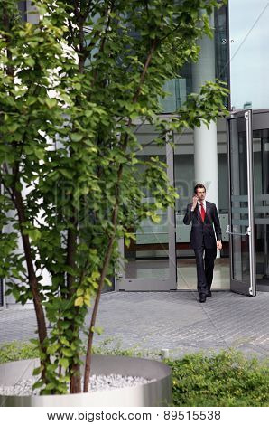 young caucasian businessman at office exterior talking on cellphe