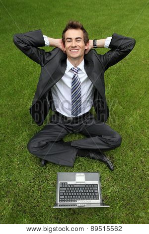 young caucasian businessman relaxing on grass with his laptop