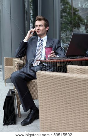 young caucasian businessman using his laptop in cafe - drinking
