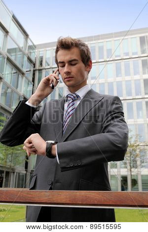 portrait of young confident caucasian businessman talking on cellphone