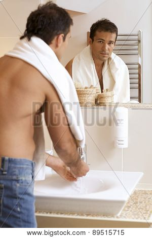 Young man washing his hands in sink