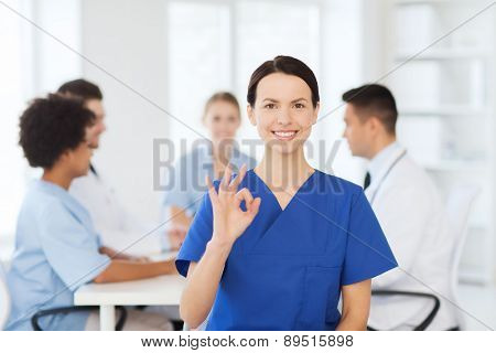 clinic, profession, people and medicine concept - happy female doctor over group of medics meeting at hospital showing ok hand sign