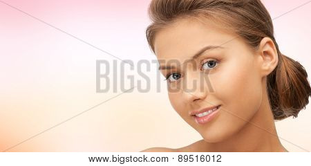 beauty, people and health concept - beautiful young woman face over pink background