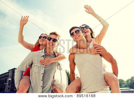 holidays, vacation, love, gesture and friendship concept - smiling couple having fun and waving hands in city