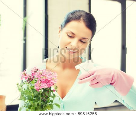 young woman holding pot with flower and spray bottle