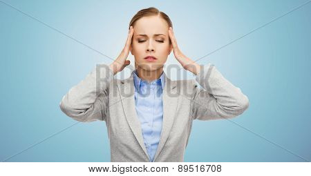 business, medicine, health and people concept - stressed businesswoman having headache and touching head over blue background