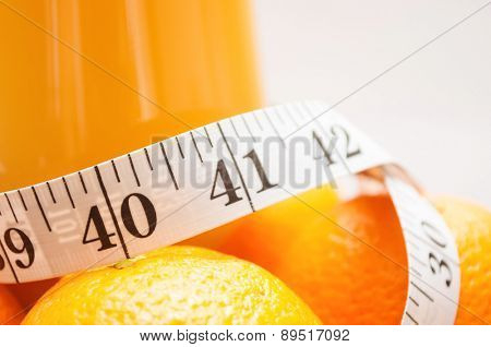 Close up shot of measuring tape in inches, around oranges and glass of juice