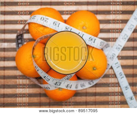 Orange juice and fresh oranges around glass wrapped with measuring tape