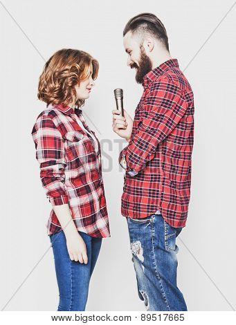 Karaoke - Lovely couple with microphone. Young and beauty. Hipster style. Over white background.