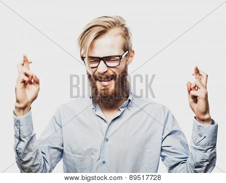Portrait of young bearded man wearing glasses in shirt keeping fingers crossed and eyes closed while standing against white background&