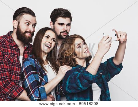 education, technology and people concept: group of students taking selfie with smartphone  over white background.Special Fashionable toning.