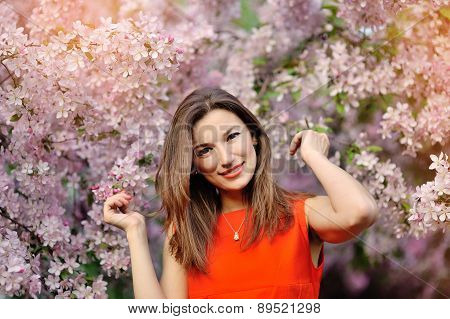 Beautiful Girl In Red Dress And Flowering Trees