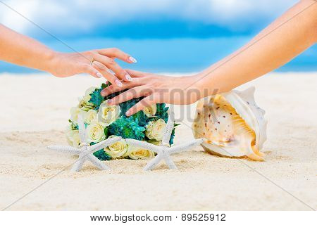 Male And Female Hands, Two Wedding Rings With Two Starfish, Wedding Bouquet And A Large Shell