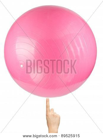 Pink Pilates Ball At Tip Of Finger