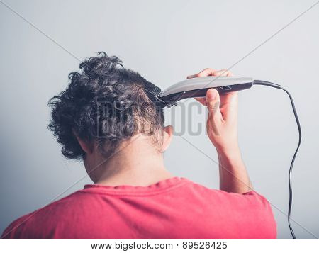 Young Man Cutting His Hair At Home