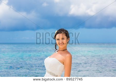 Beautiful Fiancee In White Wedding Dress Stand On Shore Sea. Wedding And Honeymoon In The Tropics.