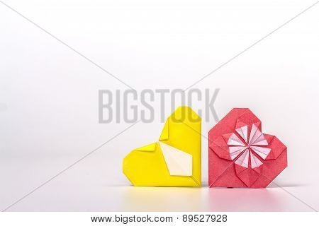 Photo of two origami hearts - red and yellow.