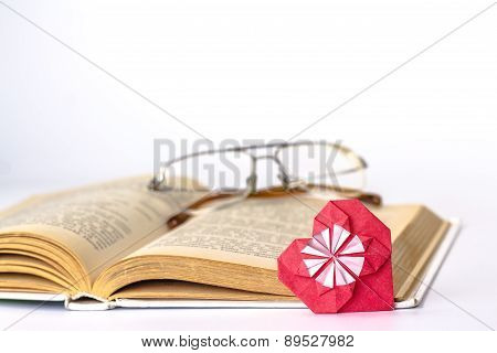 red origami paper heart and glasses over open book