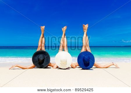 Three Young Women In Straw Hats Lying On A Tropical Beach, Stretching Up Slender Legs.
