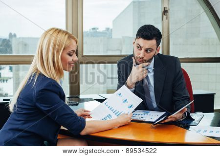 Businessman And Businesswoman Looking At Business Document