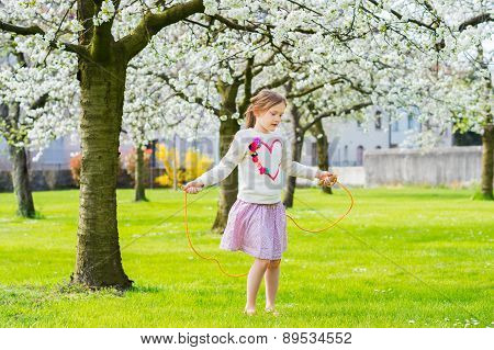 Pretty little girl playing in a spring garden, jumping with skipping rope