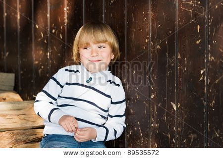 Cute little caucasian blond boy leaning on an old wooden wall, wearing white pullover