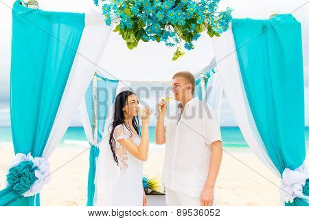 Wedding Ceremony On A Tropical Beach In Blue. Happy Groom And Bride Drinking Champagne