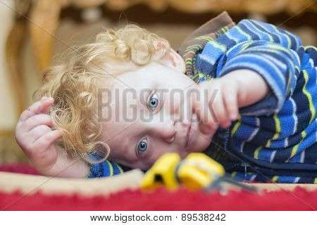 Little Boy Playing With Toy On The Floor