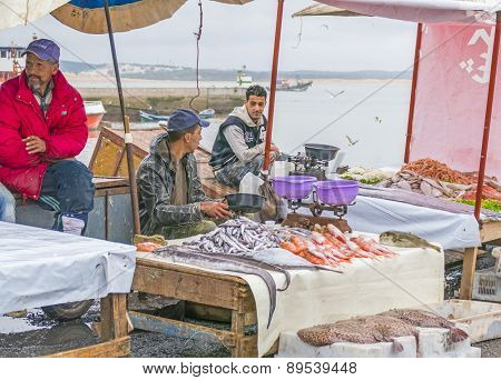 AS-SAWIRA, MOROCCO, APRIL 7, 2015: Fishermen sell fish and seafood in port of As-Sawira
