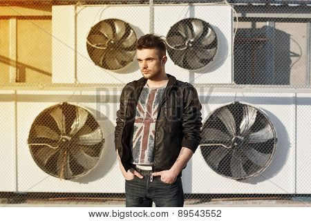 Beautiful Guy In A Black Leather Jacket. Stands Near Blades.