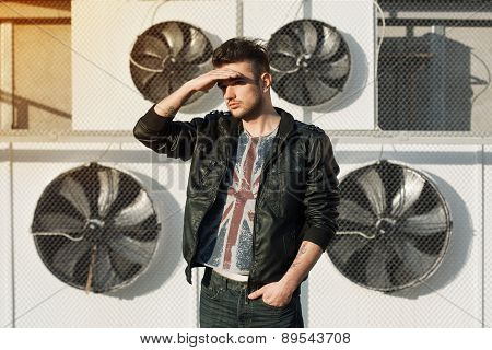 Beautiful Guy In A Black Leather Jacket. Stands Near Air Conditioners. Looks Into The Distance.