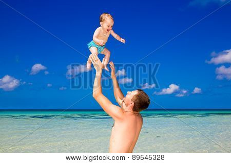 Happy Father And Child Having Fun On A Tropical Beach. Summer Vacation Concept.