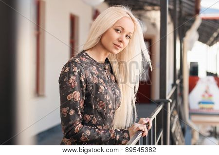 Beautiful Woman In Leather Jacket With Flowers Standing Near The Railing. Spring.