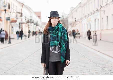 Portrait Of A Beautiful Girl In A Black Cloak With A Scarf Standing On The Square. People Walking Ar