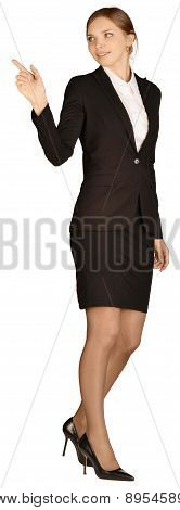 Young girl dressed suit shows forefinger in the empty space