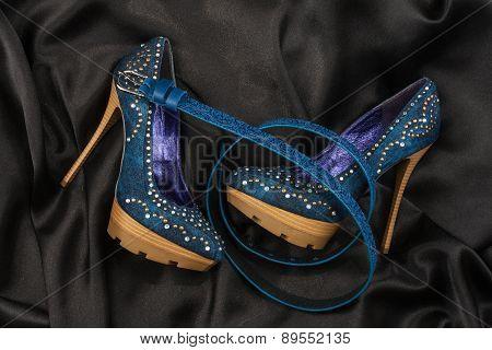Blue Shoes And Belt  Lying On Black Satin